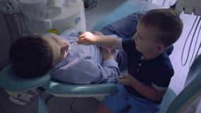 Peu garçon jouant un docteur et un type adolescent s'asseyant dans la chaise dans le bureau de dentiste Enfant inspectant des den banque de vidéos
