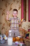 Peu garçon mangeant un tarte dans la cuisine photo libre de droits