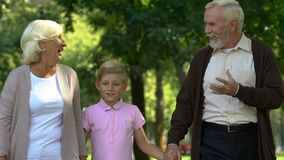 Peu garçon marchant avec ses grands-parents en parc, appréciant le temps heureux ensemble banque de vidéos