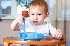 Peu garçon mignon apprenant à manger avec une cuillère lui-même dans la cuisine Concept d'aliment pour bébé sain photographie stock libre de droits
