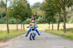 Peu garçon mignon d'enfant sur la bicyclette l'été ou le jour d'autmn Enfant heureux en bonne santé ayant l'amusement avec le rec Image stock