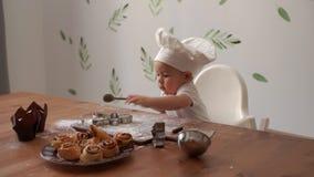 Peu garçon mignon dans le chapeau d'un chef recherche et commence à créer dans la cuisine clips vidéos