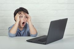 Peu garçon observant le contenu inadéquat sur l'ordinateur portable photos stock