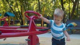 Peu garçon poussant le carrousel clips vidéos