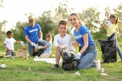 Peu garçon rassemblant des déchets avec le volontaire photos stock