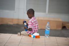 Peu garçon s'asseyant sur une terrasse avec une bouteille de l'eau à disposition photographie stock