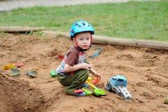 Peu garçon sur le bac à sable avec des jouets photo stock