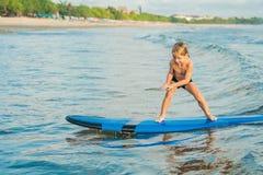 Peu garçon surfant sur la plage tropicale Enfant sur le panneau de ressac sur le ressac Sports aquatiques actifs pour des enfants photo libre de droits