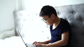Peu garçon utilisant l'ordinateur portable se renseignant sur la technologie à la maison pour l'éducation banque de vidéos