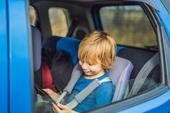 Peu garçon voyageant sur la banquette arrière d'une voiture utilisant le pavé tactile pour s'amuser pendant le voyage images stock