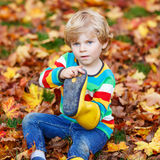 Peu garçons mignons de garçon d'enfant s'étendant dans des feuilles d'automne dans des clo colorés Photos stock