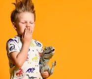 Peu gar?on avec des cheveux dr?les et en d?sordre tient le dinosaure en plastique de jouet comme portrait photos stock