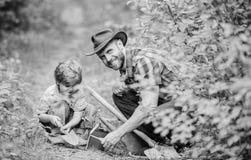 Peu gar?on et p?re ? l'arri?re-plan de nature Outils de jardinage neufs, plateau de canne Passe-temps de jardinage Papa enseignan photo libre de droits