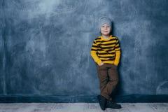 Peu gar?on ? la mode posant devant un mur en b?ton gris-bleu Portrait d'un enfant de sourire habillé dans un noir et jaune photographie stock