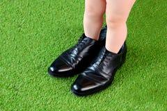 Peu jambes d'enfant de garçon dans des chaussures élégantes du père photographie stock