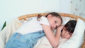 Peu la fille que mignonne est tombée endormi dans la chaise, soeur la caresse, mouvement lent banque de vidéos