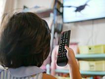 Peu la main du bébé asiatique jugeant une télévision à télécommande, tout en l'observant à la maison photographie stock