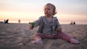 Peu les jeux bouclés de fille dans le sable avec une spatule marche sur la plage en mer banque de vidéos
