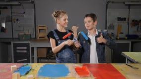 Peu maîtrise au travail Petits concepteurs Conseils de peinture adorables de frère et de soeur avec des rouleaux de peinture dans banque de vidéos