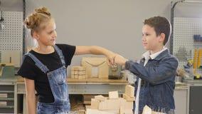 Peu maîtrise le concept Tir des enfants dans l'espace de travail de bâtiment fonctionnant ensemble Amis un garçon et un poing de  banque de vidéos