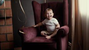 Peu montées mignonnes de bébé garçon sur ses propres moyens sur le beau fauteuil dans le mouvement lent clips vidéos