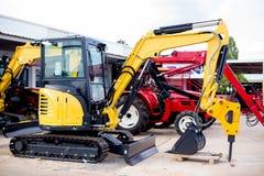 Peu nouvelle excavatrice jaune sur des voies photo stock