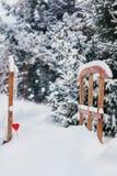 Peu pont en bois sous la neige décorée du coeur lu dans l'allée brouillée de pins d'hiver avec la neige en baisse photos stock