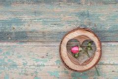 Peu s'est levé et le coeur découpé en bois sur le vieux grunge a peint b Photographie stock