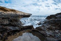 Peu vague se brisant dans la côte photographie stock