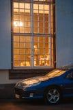 Peugeot-auto onder verlicht venster wordt geparkeerd dat Stock Fotografie