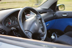 Peugeot 206 coupe cabriolet parked in the park. Peugeot 206 cc leather steering wheel and front dashboard, manufactured in 2004. Photographed on a nice sunny day Stock Image