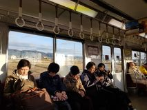 Peuple japonais s'asseyant dans le train local le soir à la station de Kyoto image stock