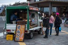 Peuple japonais wating pour manger le gril de beurre de pain photos stock