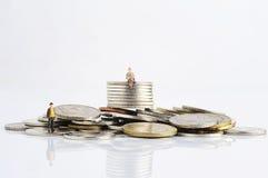 Peuples miniatures avec des pièces de monnaie Images stock