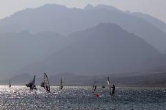 Peuples sur le windserf en contre-jour et montagnes Images libres de droits