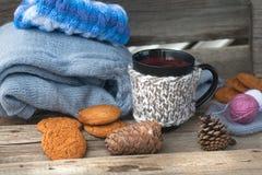 Peut avec la boisson chaude et les vêtements le tricotage Photographie stock libre de droits
