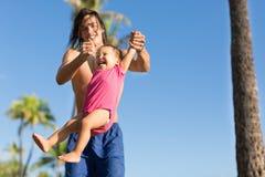 Peuter die een grote tijd met zijn oom in het park op een zonnige dag hebben Royalty-vrije Stock Fotografie