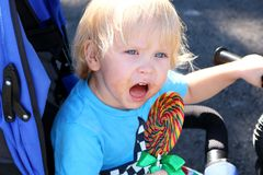 Peuter die een yummy kleurrijke lolly eten Babyjongen met wervelingslolly Stock Afbeeldingen