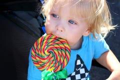 Peuter die een yummy kleurrijke lolly eten Babyjongen met wervelingslolly Stock Fotografie