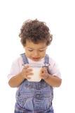 Peuter die melk in glas bekijkt stock afbeeldingen
