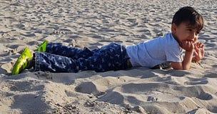 Peuter die op strand van zon genieten Stock Foto's