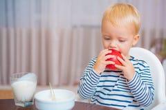 Peuter die snack hebben thuis Het kind eet havermoutpap Blauwe ogen van de jong geitje zitten de leuke jongen bij lijst met plaat royalty-vrije stock afbeeldingen