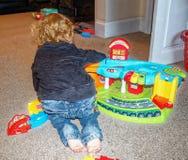 Peuter het spelen met stuk speelgoed auto's en stuk speelgoed garage Stock Foto