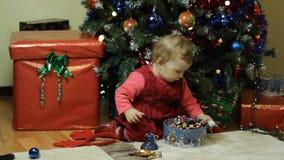 Peuter het spelen naast een Kerstboom stock videobeelden
