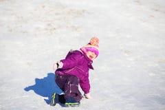 Peuter het spelen op een heuvel in de winter Stock Foto