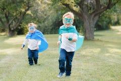 Peuter Kaukasische kinderen die superheroes spelen stock afbeelding