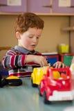 Peuter in klaslokaal het spelen met speelgoed Stock Foto's