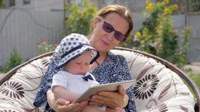 Peuter met de tablet van de grootmoederholding Gelukkig familieconcept Grootmoeder met kleindochter stock videobeelden
