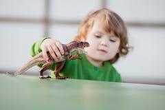 Peuterjong geitje het spelen met een stuk speelgoed dinosaurus stock fotografie