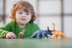 Peuterjong geitje het spelen met een stuk speelgoed dinosaurus royalty-vrije stock fotografie